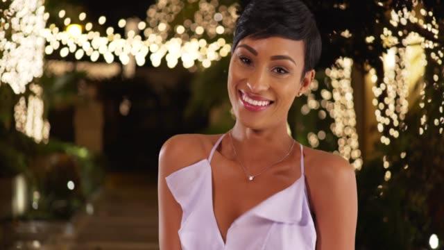 vidéos et rushes de gorgeous young black woman in lilac dress smiling at camera on summer night - robe d'été