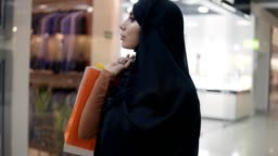 Gorgeous young muslim woman in black hijab with different bags on her shoulder walking by shopping mall. Slow motion. Arabic, confident woman enjoying shopping time, smiling