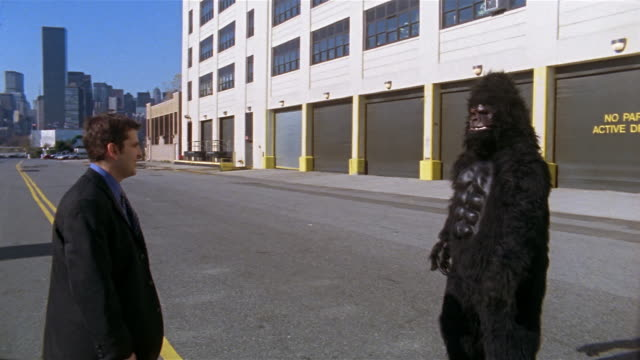 Gorilla and businessman giving each other high five in middle of empty street / New York City
