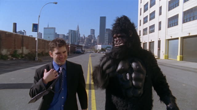 Gorilla and businessman having conversation in middle of empty street with view of Manhattan skyline in background / Long Island City, Queens, New York City