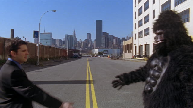 Gorilla and businessman shaking hands in middle of empty street with view of Manhattan skyline in background / Long Island City, Queens, New York City