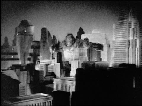 vidéos et rushes de b/w gorilla (costume) walking amongst city buildings (miniature) toward camera / zoom in - 1933