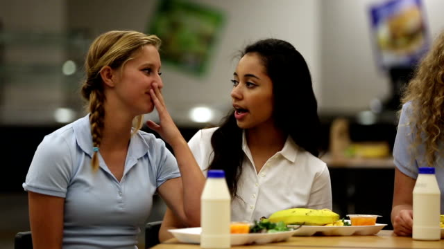 gossipy girls talking about other girl in school cafeteria - female high school student stock videos and b-roll footage