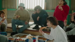 Goup of young Japanese skateboarders eating pizza during skateboard session