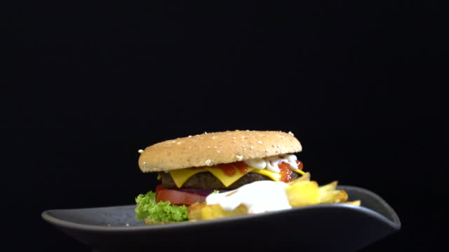 Gourmet cheeseburger with potatoes,tomato,onion,on the rotating table