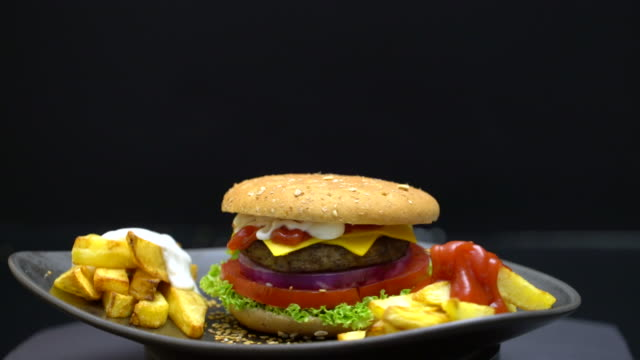 gourmet cheeseburger with potatoes,tomato,onion,on the rotating table - cheeseburger stock videos & royalty-free footage