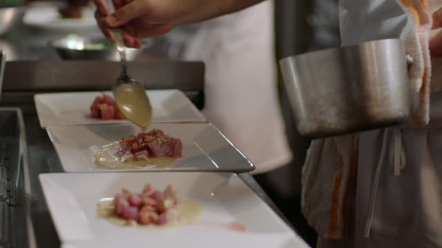 gourmet chef ladles sauce over steaming scallop dish in restaurant kitchen - gourmet küche stock-videos und b-roll-filmmaterial