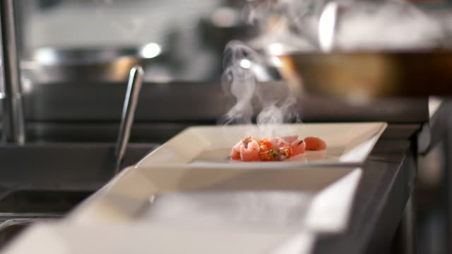 gourmet chef ladles steaming scallops onto dinner plates in restaurant kitchen - gourmet küche stock-videos und b-roll-filmmaterial