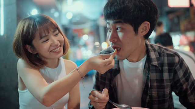 gourmet couple tasted street food at the food stalls in night food market. - market stall stock videos & royalty-free footage