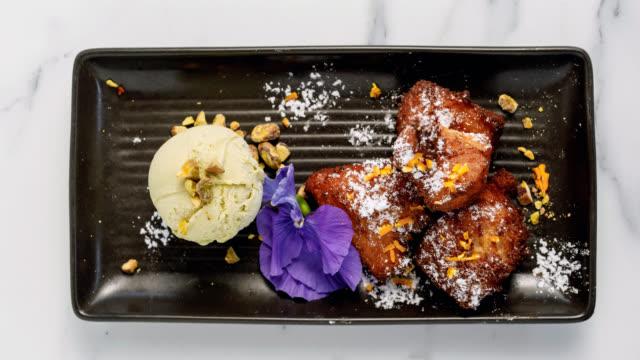 gourmet dessert - ricotta doughnuts with pistachio gelato - dessert topping stock videos & royalty-free footage