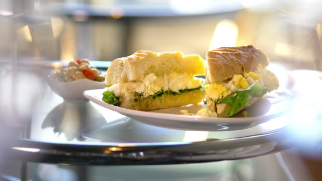 Gourmet egg salad sandwich, cut in half, in bright sunny restaurant