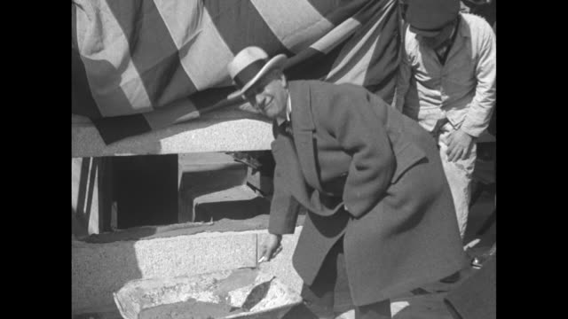 stockvideo's en b-roll-footage met gov al smith bending over and using trowel to spread mortar beneath suspended cornerstone / smith standing next to cornerstone as it is lowered into... - al smith