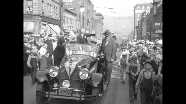 gov al smith standing next to train waving his hat at crowd / three shots of smith standing in back seat of open car as it drives down street at head... - hands behind head stock videos & royalty-free footage
