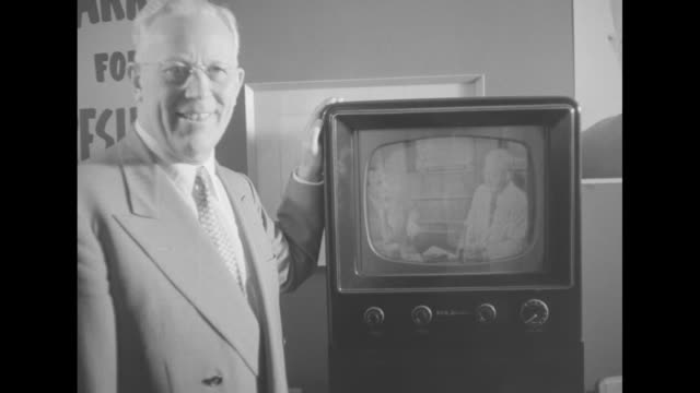 CA Gov Earl Warren standing in room next to television set watching convention coverage on television he smiles poses for photo / two shots of Warren...