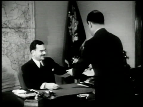 Gov Thomas E Dewey at desk looking at papers WS Dewey at desk assistant CU Dewey signing signature on paper MS Lawyer John Foster Dulles at desk...