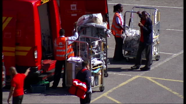 Government accused of undervaluing Royal Mail shares R10071314 / TX Postmen loading vans Post delivery vehicles along