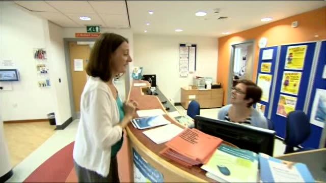 Government announces GP surgeries longer hours pilot scheme ENGLAND Greater Manchester INT Female patient talking to receptionist in GP surgery...
