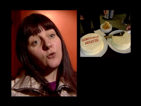 government approves gm crops; itv evening news: chris choi itn england: london: int two cakes on a table one of them has 'genetically modified' iced... - itv evening news stock-videos und b-roll-filmmaterial