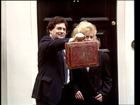 government attacks labour party over tax changes ext downing st cms nigel lawson holding up budget box as standing with wife therese for photocall - budget stock-videos und b-roll-filmmaterial