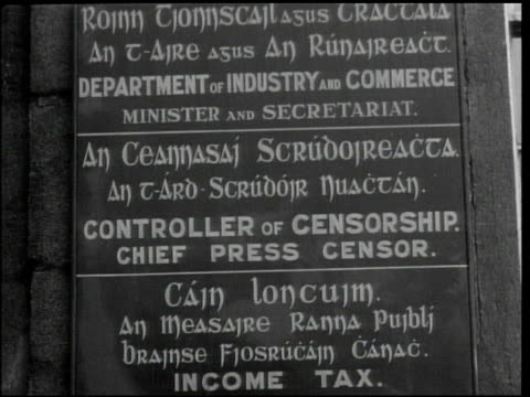 vídeos de stock e filmes b-roll de government building ms bilingual sign 'controller of censorship' vs men in office reading newspapers copy of article clipping stamped 'passed' cu... - 1944