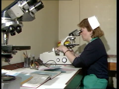 government campaign; england: int technician looking through microscope tcbv ditto - microscope stock videos & royalty-free footage