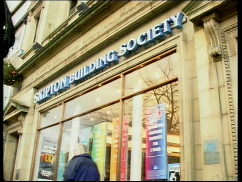 government crackdown on building society windfalls; itn england: yorkshire: skipton: ext/evening gv town square people along past market stall bv... - スキップトン点の映像素材/bロール