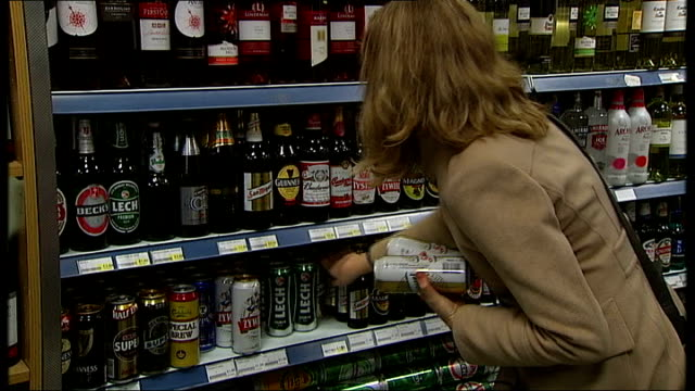 government criticised over minimum price increases to alcohol; int woman taking cans of lager from shelf bottles of wine on display in shop - lager stock videos & royalty-free footage