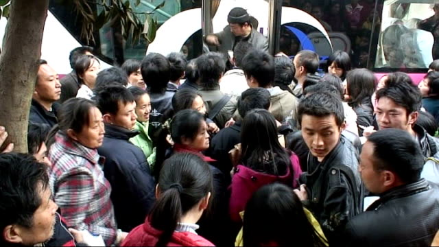 Government forced to act to counter threat of recession DAY Chinese migrant workers crowding round bus Migrant workers carrying belongings in wicker...
