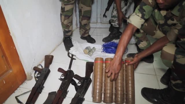 Government forces examine weapons seized after they were abandoned by rebels on the Comoros island of Anjouan