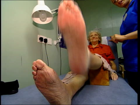 government health service reforms announced / another leak to press:; residential home: gv elderly woman with leg in cast watched by nurse as she... - ギプス点の映像素材/bロール