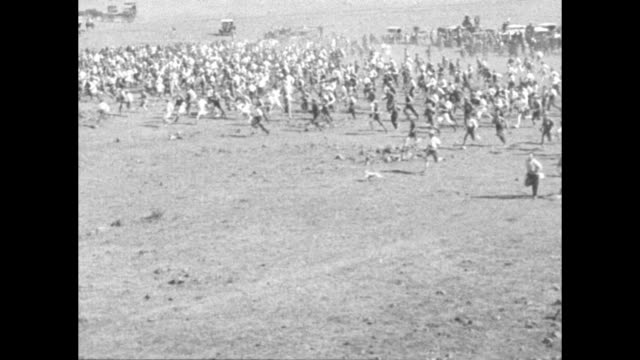 Government officials on horseback keep crowd in line / closer shot crowd of men / various shots looking down on men running across open field / pan...
