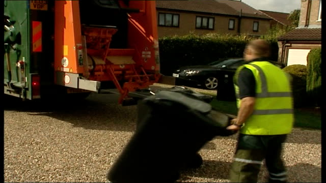 Government outlines strategy to deal with excess waste Refuse collectors collecting rubbish bins Close up microchip held in hand Rubbish bins outside...