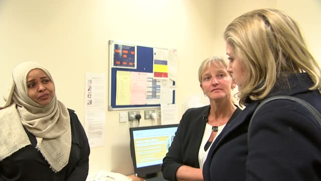government pledges more money to tackle female genital mutilation england london int penny mordaunt mp meeting people during visit to health centre - mutilazioni genitali femminili video stock e b–roll