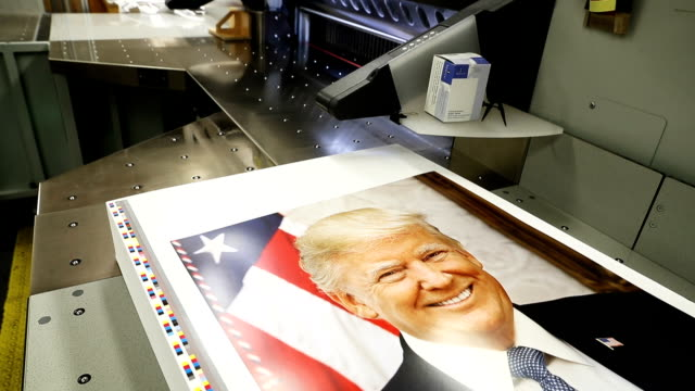 US Government Publishing Office bookbinder Daniel Kinney trims the edges off copies of the official photograph of President Donald Trump December 4...