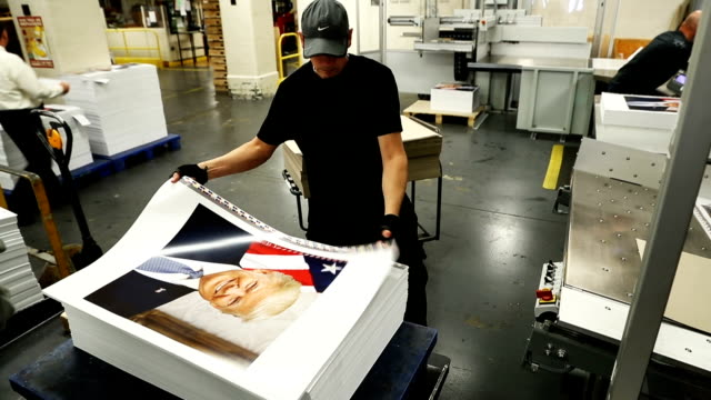 Government Publishing Office bookbinder Ronny Varnell stacks copies of the official photograph of President Donald Trump December 4 2017 in...
