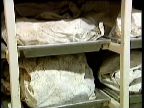 Government report denies Srebenica massacre happened LIB Wrapped bodies on morgue shelves TILT UP BV Man away past shelves of corpses TRACK