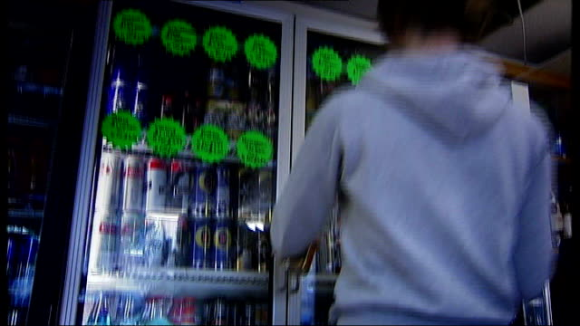 government uturn on minimum alcohol pricing t12081011 / tx greater manchester stockport int woman places lagar can on shelf in shop refrigerated unit - stockport bildbanksvideor och videomaterial från bakom kulisserna