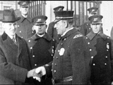 vídeos de stock e filmes b-roll de governor calvin coolidge walking in front of policemen calvin shaking hands w/ large policeman ms men in crowd waving bowler hats governor coolidge... - 1919