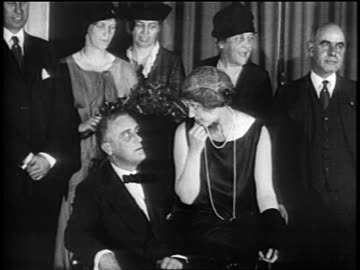stockvideo's en b-roll-footage met governor f.d. roosevelt in tuxedo sharing chair with mrs. lehman / eleanor in background / newsreel - 1928
