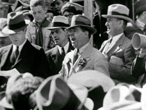 vidéos et rushes de governor huey p long in crowd keeping time to music ha pan parade w/ lsu 'tigers' football marching band vs huey adjusting 'deputy game warden'... - 1934
