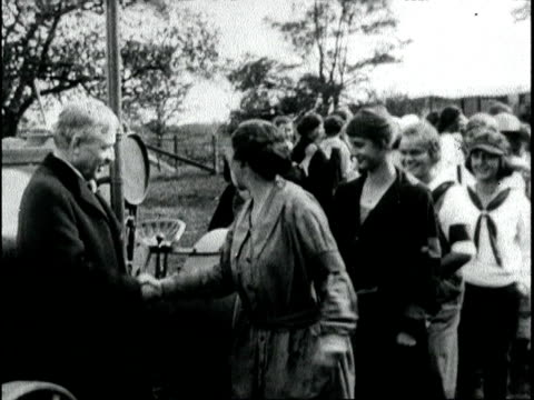 stockvideo's en b-roll-footage met governor lowden congratulats 38 girl farmer graduates many dressed in overalls he shakes their hands pretends to steer a stationary tractor and milks... - 1917