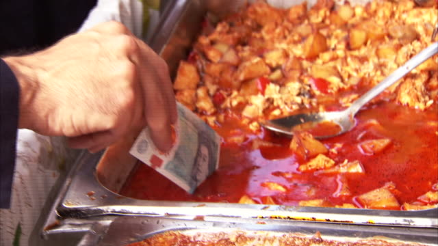 Governor of the Bank of England Mark Carney dipping the brand new polymer five pound note in chicken curry sauce to prove it is waterproof