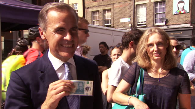 Governor of the Bank of England Mark Carney holding up the new five pound note