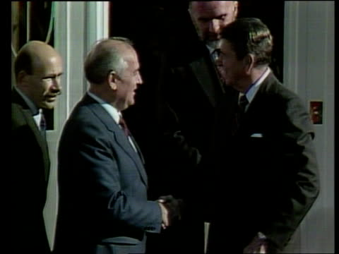 Governor's Island LA Reagan along from door of plane as waves PAN RL UN MS Gorbachev's limousine moves towards as security man precedes it PAN LR as...