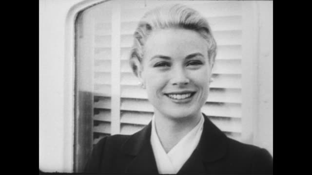 Grace Kelly arrives in Monaco aboard Prince Rainier's yacht a week before her wedding / CU Kelly smiling for the cameras / view of the yacht coming...