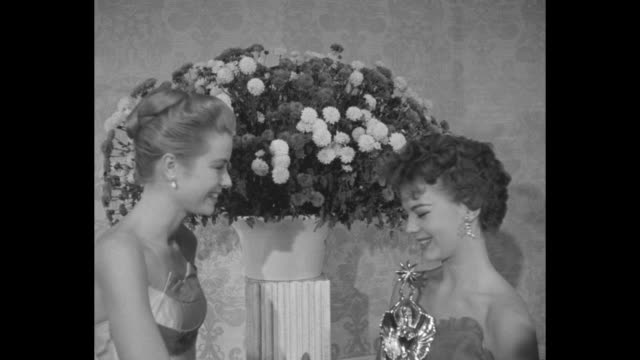 grace kelly presents award to natalie wood accepting for james dean posthumously / kelly and wood pose / audience - grace kelly actress stock videos & royalty-free footage