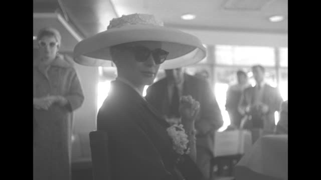 grace kelly wearing a large white sunhat flanked by her parents jack and margaret at a railing / wide shot of the ss constitution at anchor / the bow... - principe persona nobile video stock e b–roll