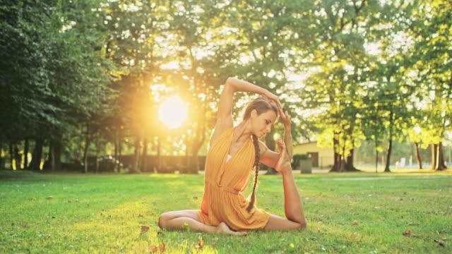 vídeos de stock e filmes b-roll de ms graceful, agile young woman practicing yoga in sunny park - descalço
