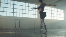 Graceful woman spinning in ballet studio