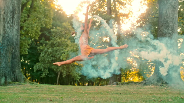 vídeos de stock e filmes b-roll de ms super slow motion graceful young woman doing jumping splits with smoke bombs in park - full length